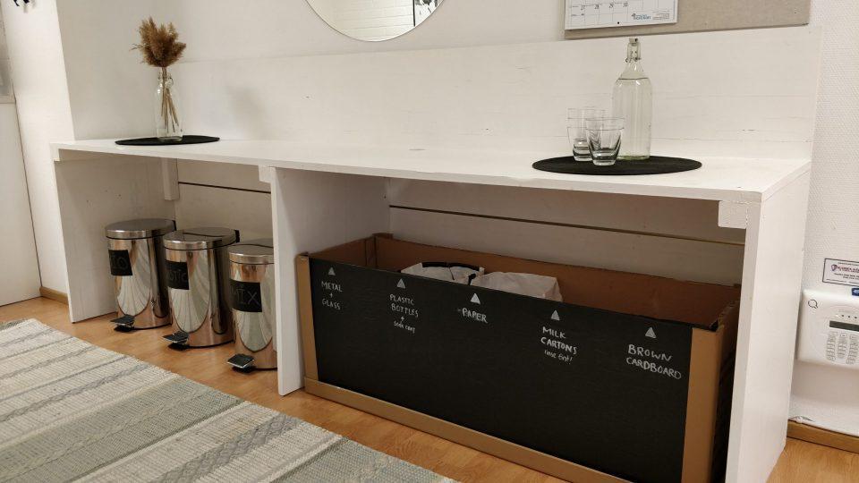 Kuva 2. Tiloissa on kokeiltu erilaisia kierrätyspisteitä, mutta käytössä paras ratkaisu on ollut uusiokäytetyn pahvilaatikon hyödyntäminen selkeän kierrätyspisteen luomiseksi.