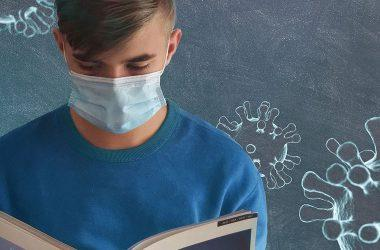 Nuori lukee kirjaa maski kasvoillaan
