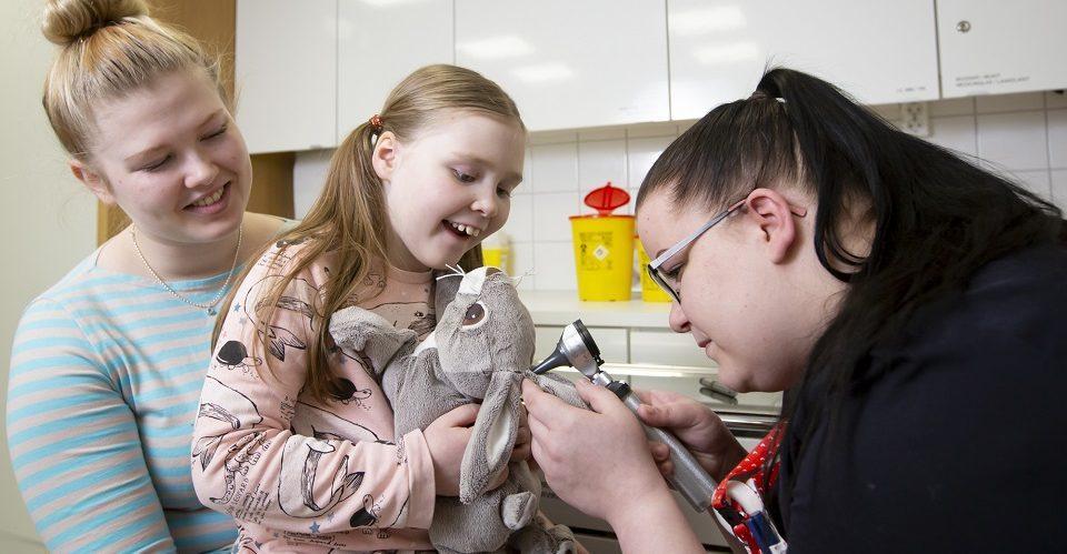 Sairaanhoitaja tutkii äitinsä sylissä istuvan tytön pehmopupun korvia korvalampulla.