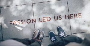 Lähikuva kahden henkilön kengistä laatoituksella, jossa teksti Passion led us here.
