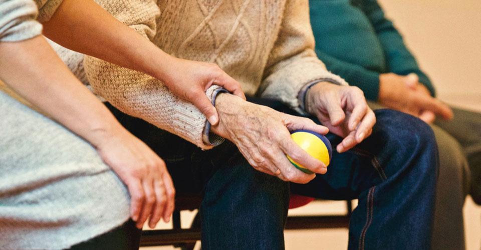 Henkilö pitää kiinni vanhemman henkilön kädestä.
