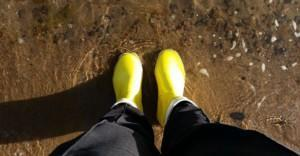 Henkilö seisoo keltaiset kumisaappaat jalassa rantavedessä.