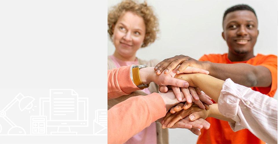 Kuvassa henkilöitä, joiden kädet on pinottu yhteen.