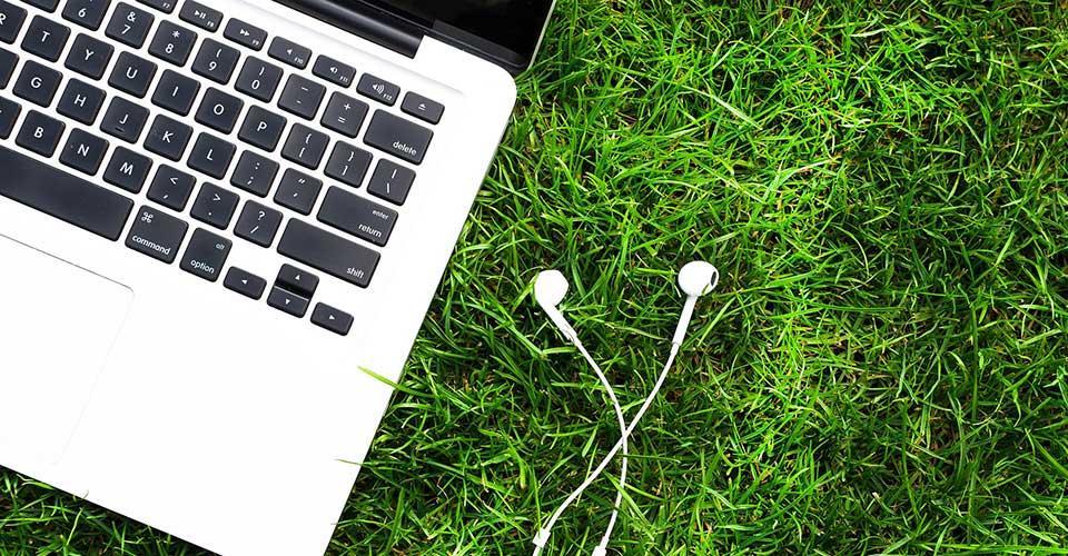 Kannettava tietokone ja kuulokkeet nurmikolla.