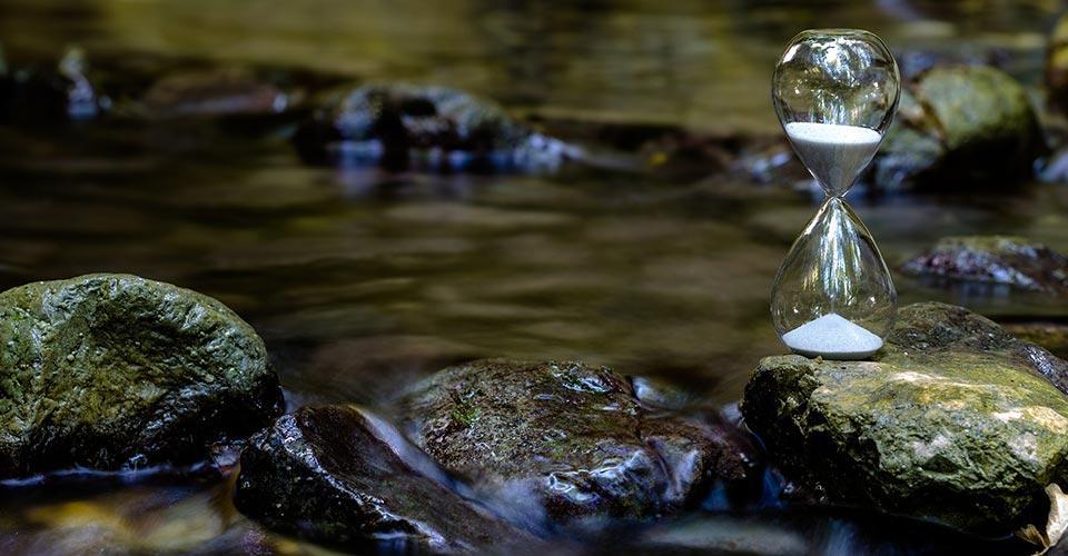 Tiimalasi kiven päällä keskellä joen virtausta.